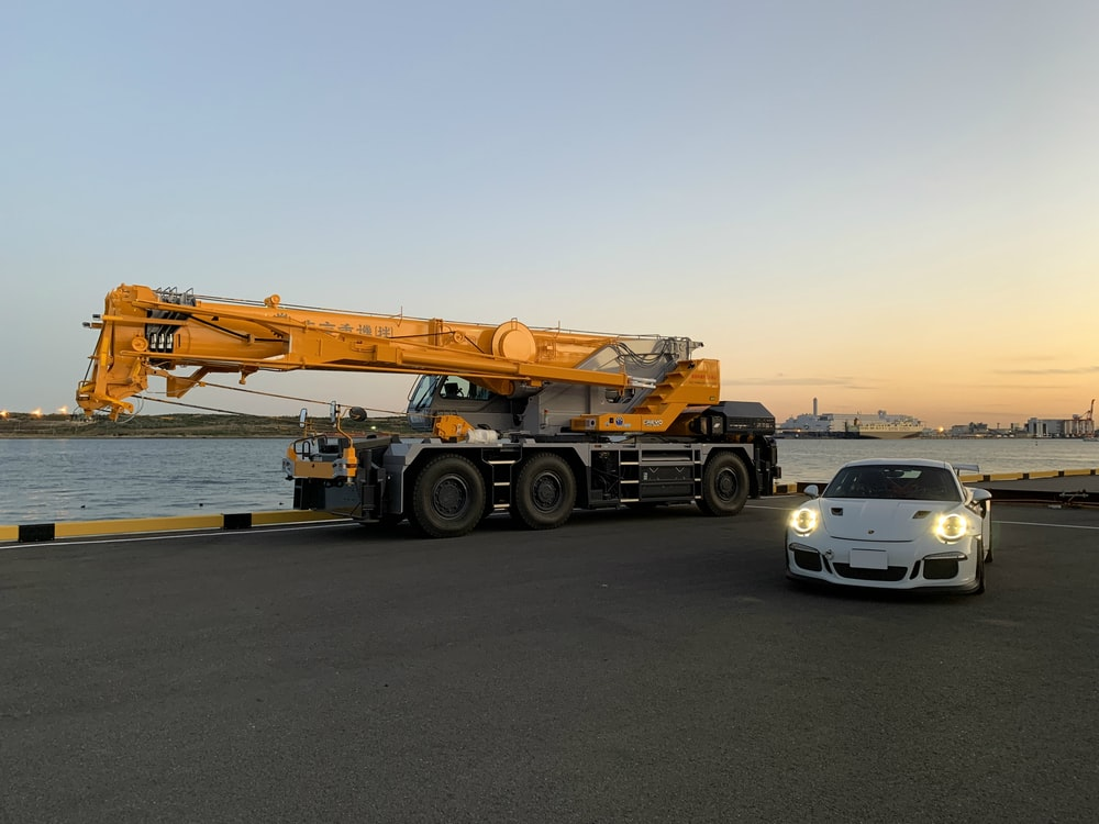 white sports car near yellow and black heavy equipment during daytime