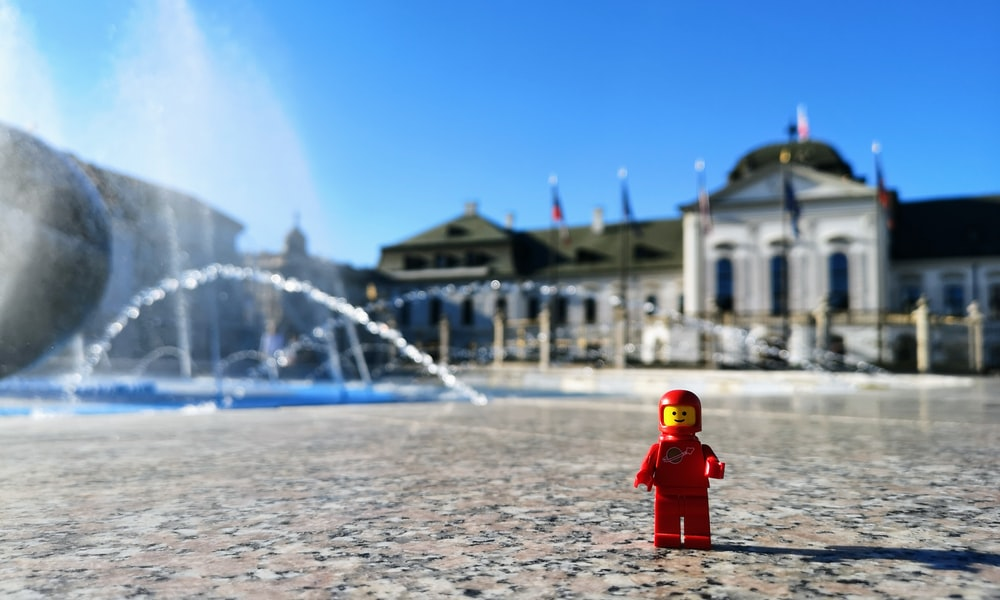 red and yellow mini figure on marble surface near water fountain