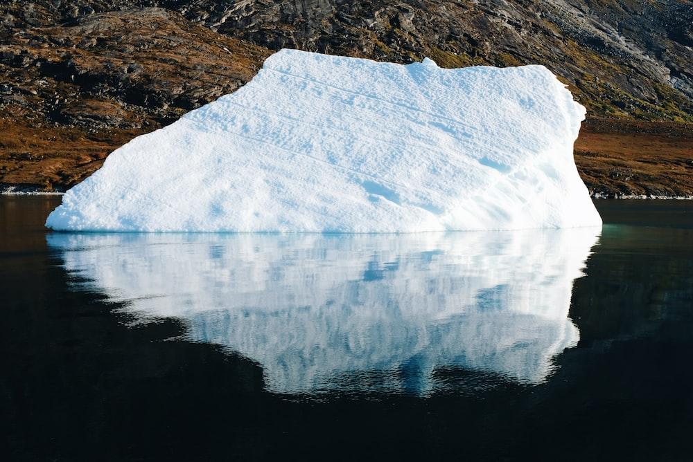 iceberg on water near mountain during daytime