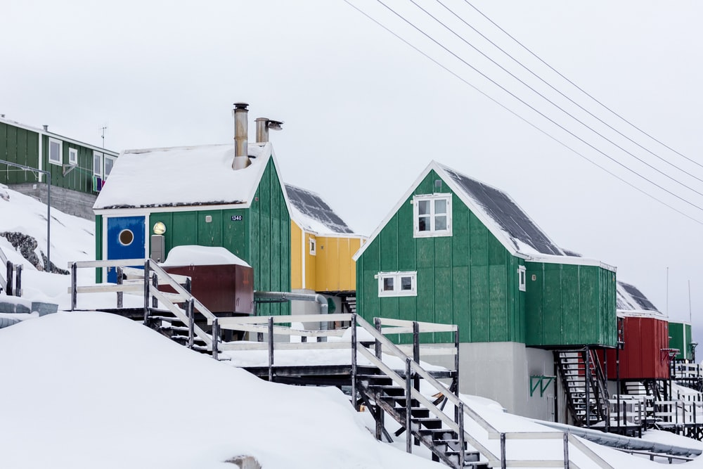green wooden houses on snow covered slope under white skies