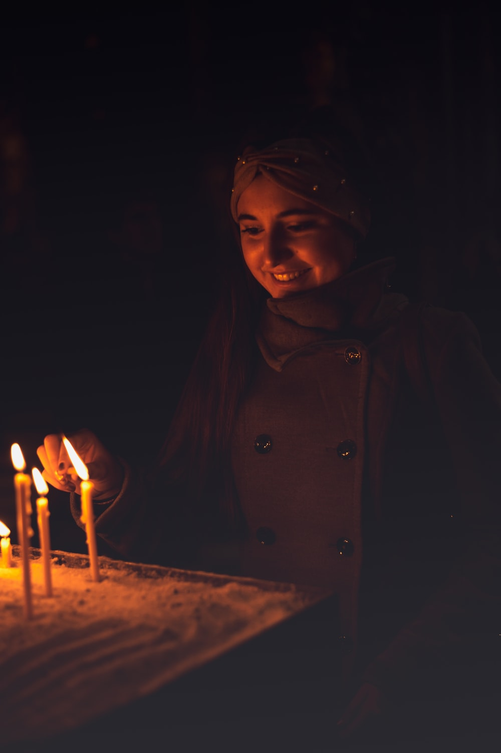 woman smiling beside lit candles