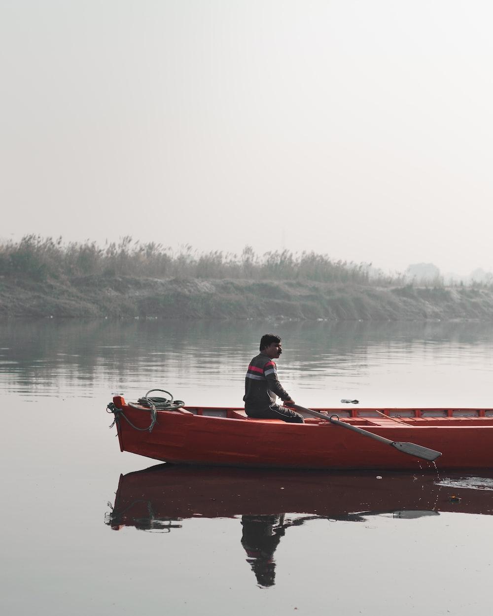man sitting on orange canoe