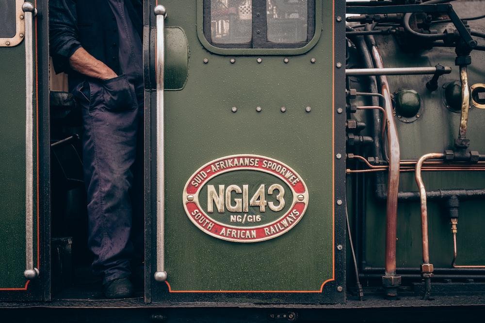man standing in green train