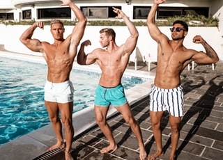three topless men standing near pool