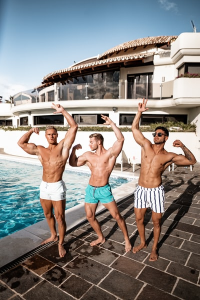 three topless men standing near pool