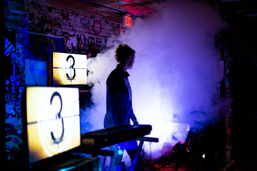 Musician among fog machine at music venue.