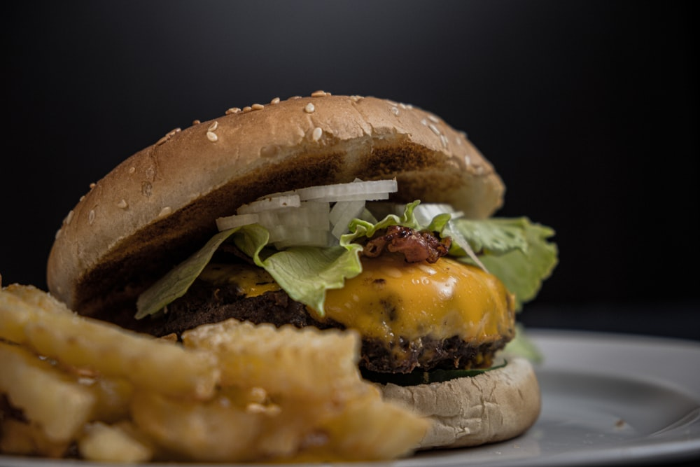 tasty burger with melted cheese and sesame seeds on top near potato fries