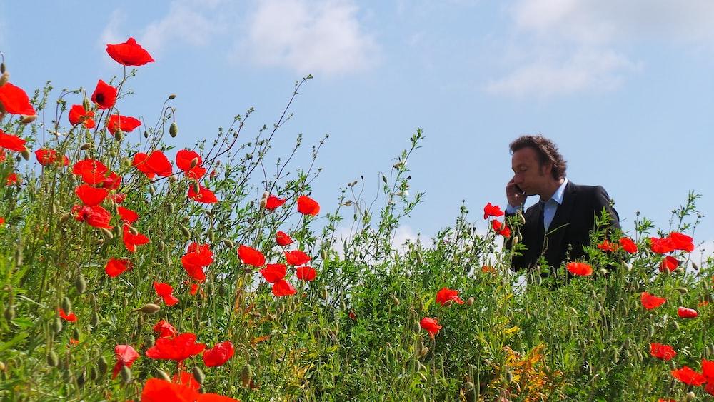 man calling on phone walking in the flower field