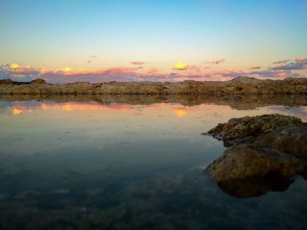rock formations on body of water viewing mountain under orange and blue sky