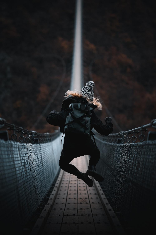 woman jumping on bridge