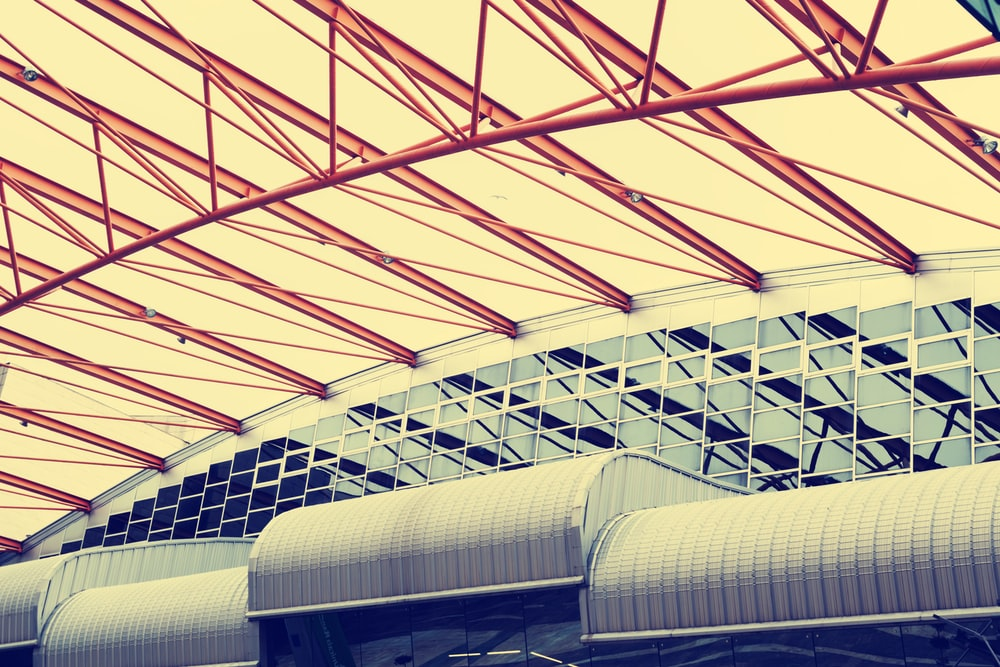 low-angle photography of red metal truss ceiling