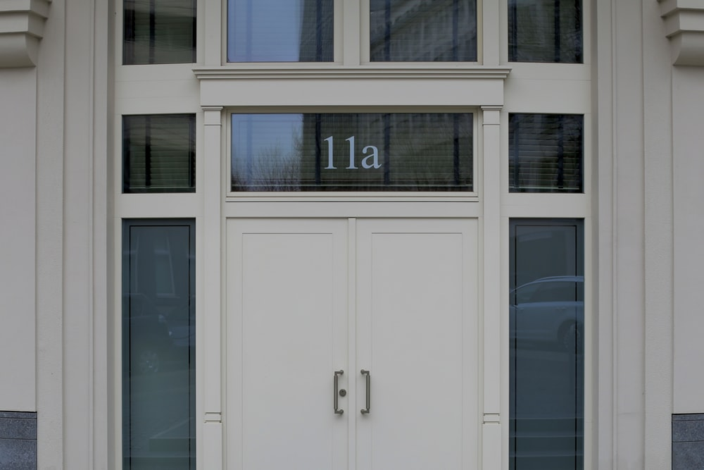 white concrete building showing closed door with 11a print