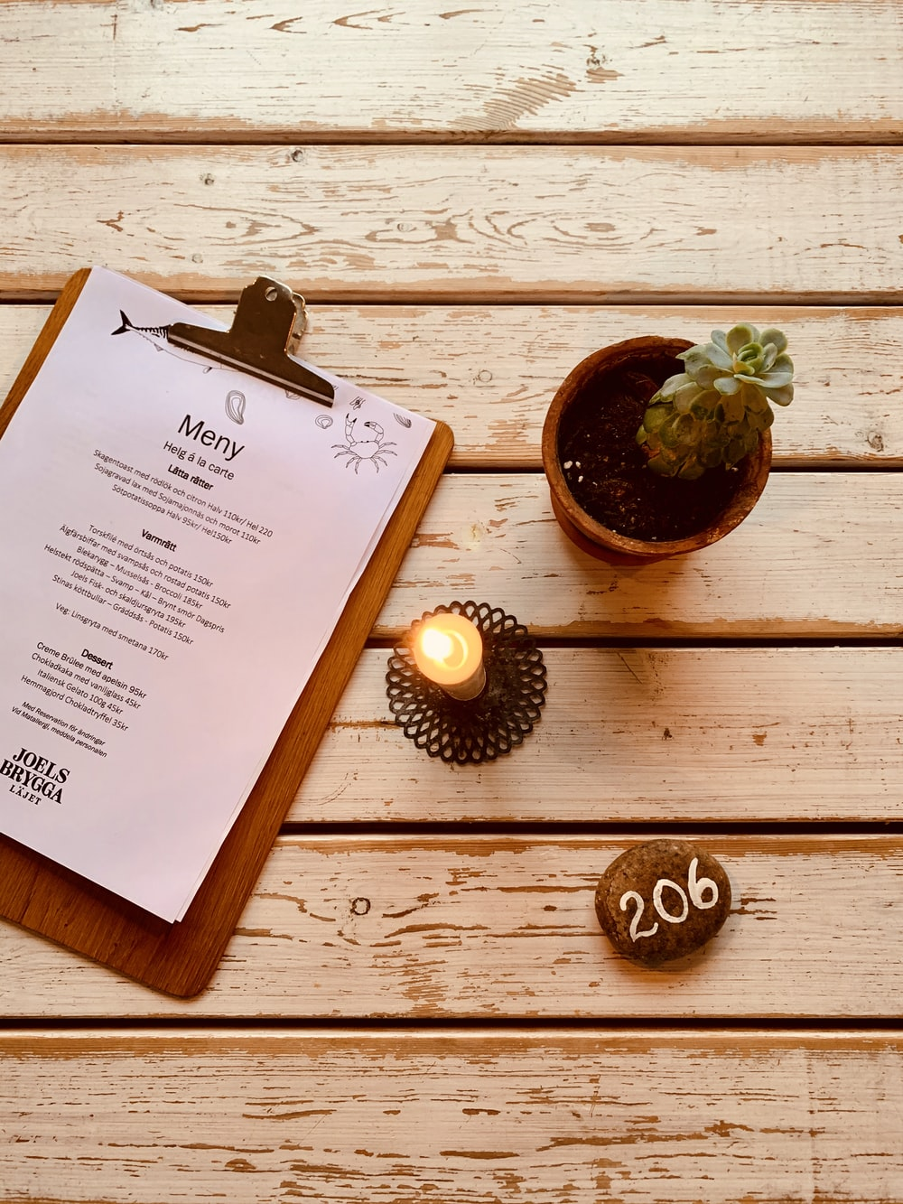 flat lay photography of a clipboard beside lighted candle and succulent