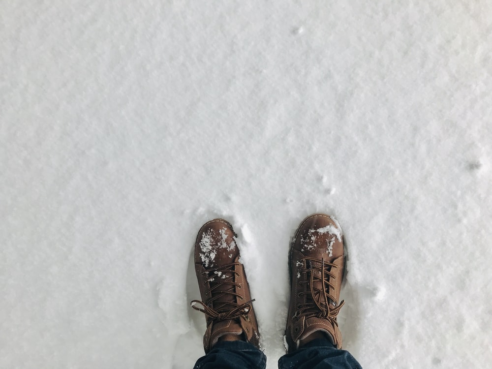 person wearing brown snow boots