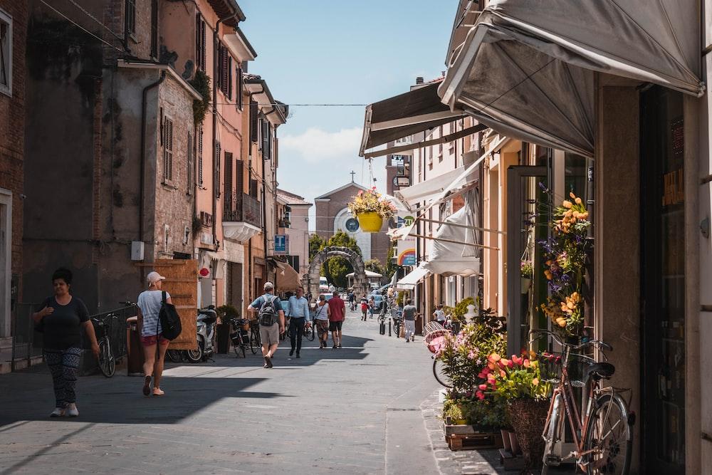 people walking on a narrow street between buildings