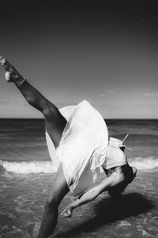 grayscale photography of woman dancing near seashore