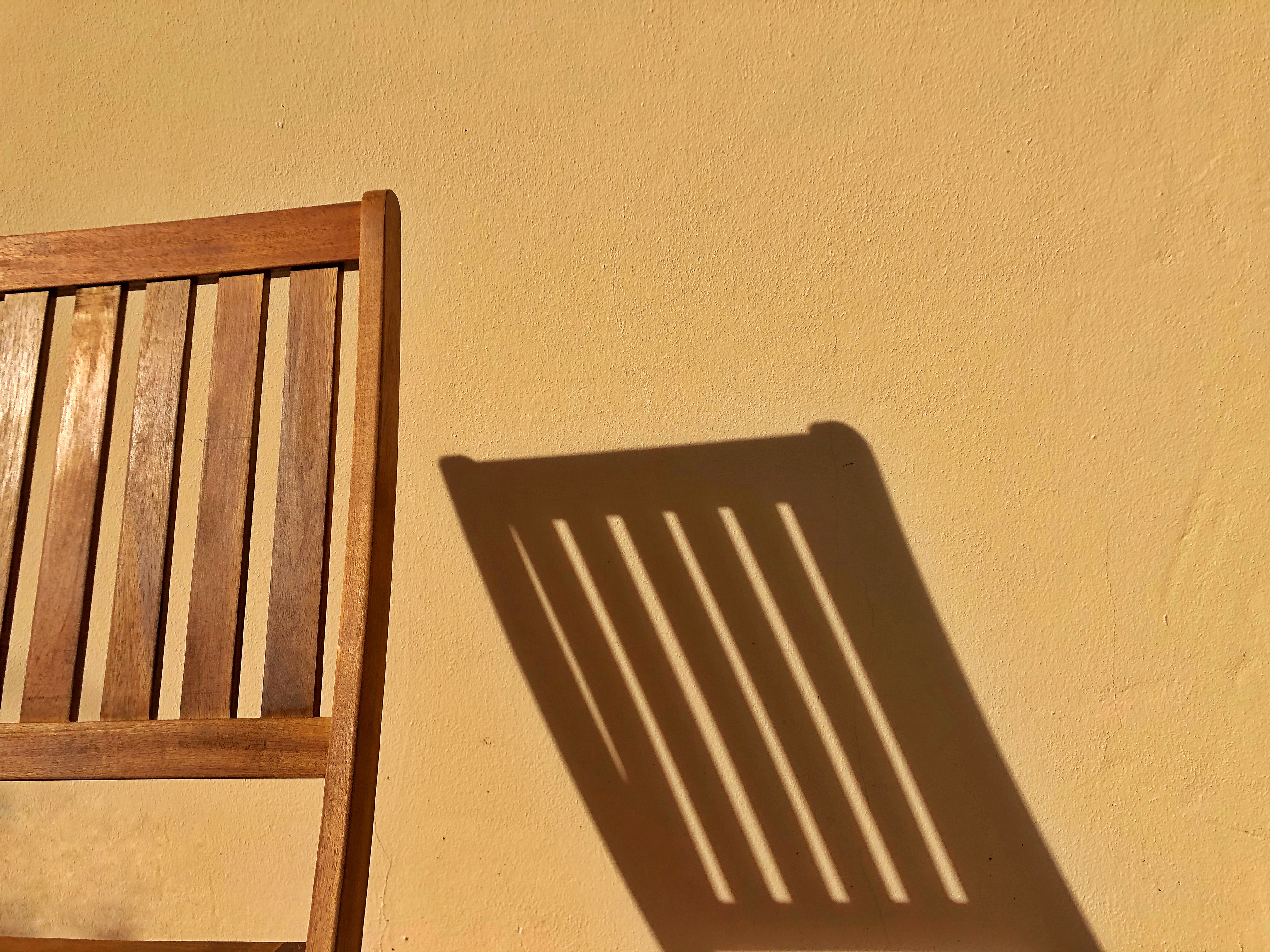 Chair and its shadow on a yellow wall