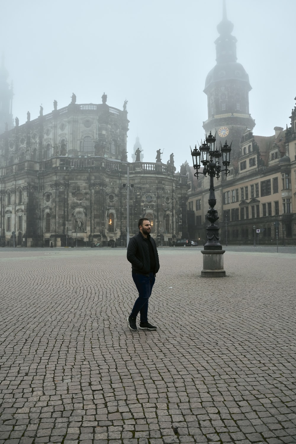 man walking near lamppost and buildings during day