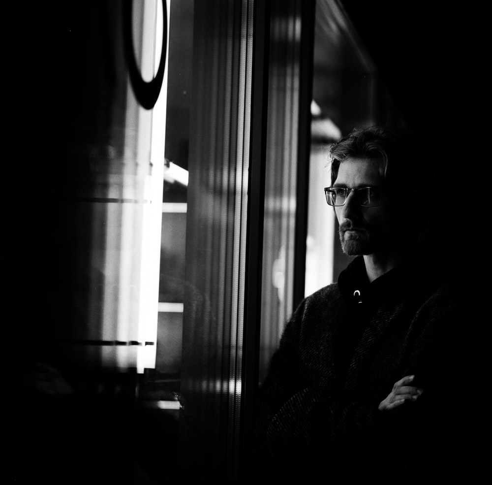 grayscale photography of man on window