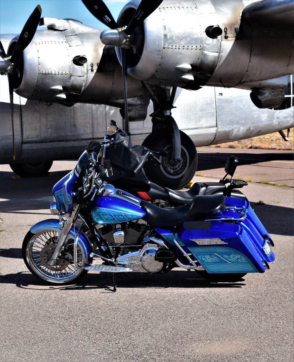 gray and black plane and blue touring motorcycle