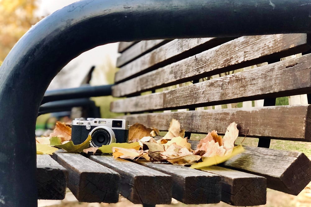 gray and black camera on brown wooden bench during daytime