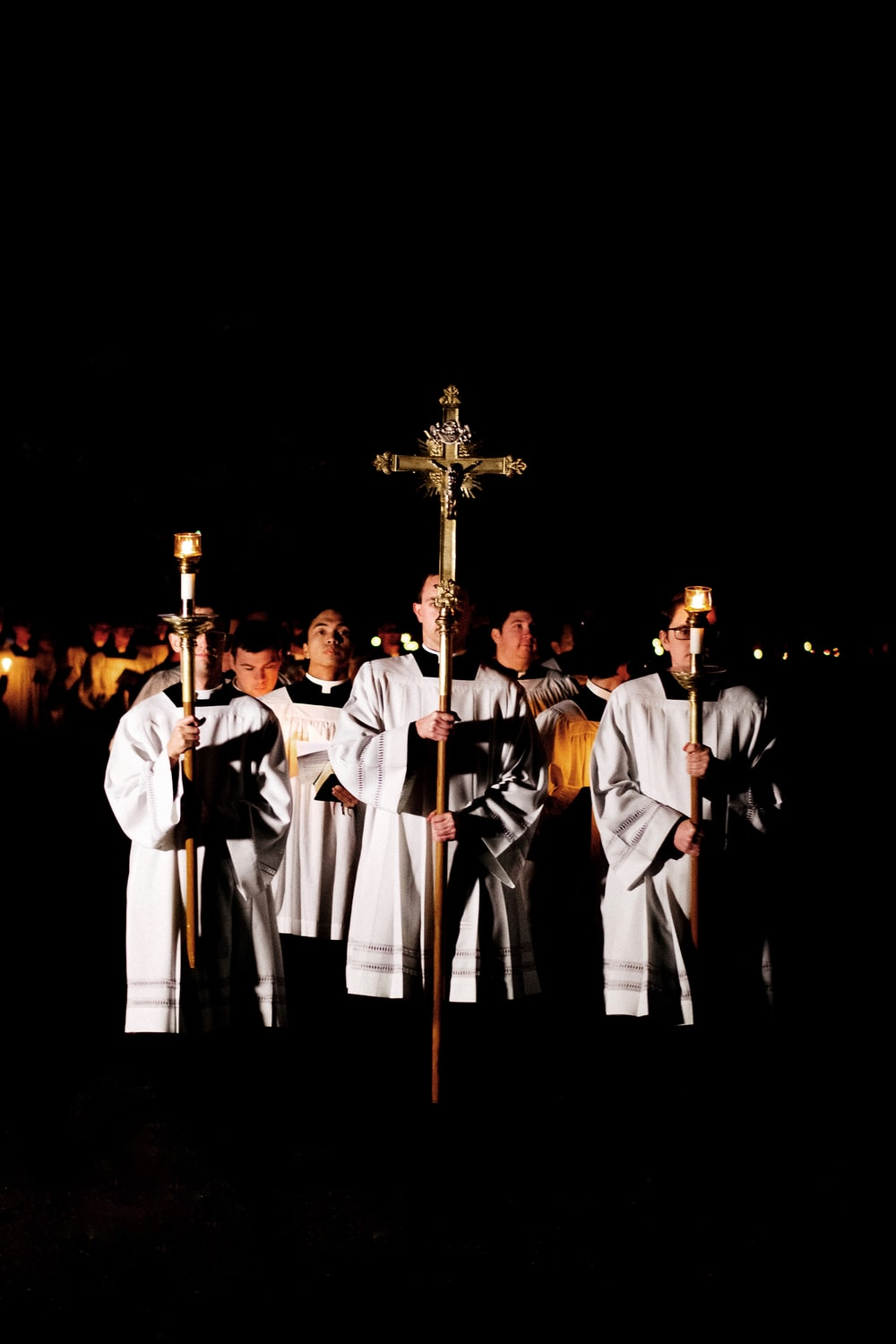 men holding cross and candle light