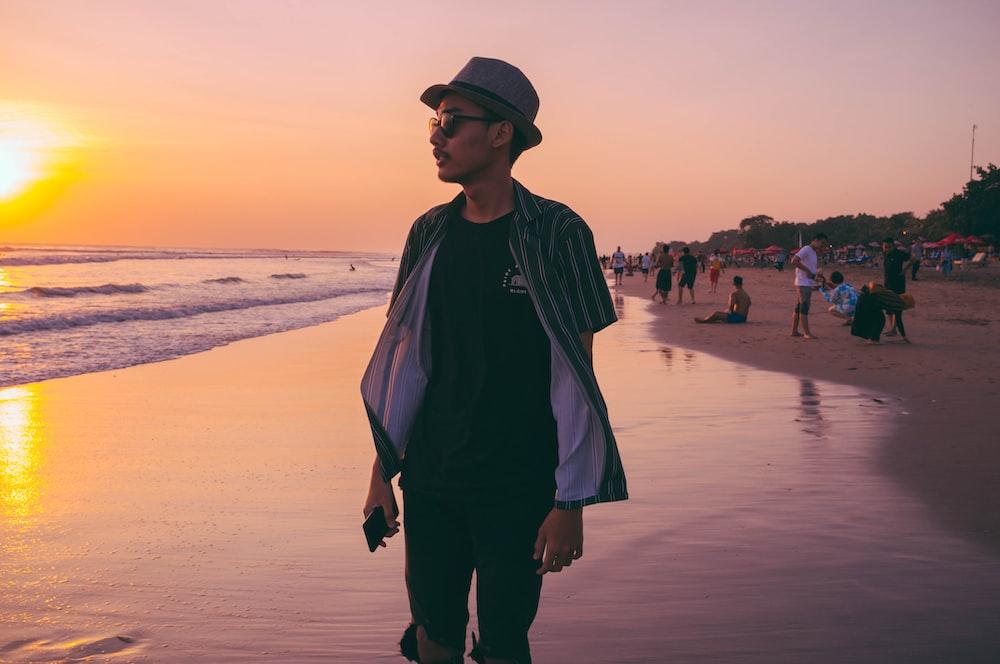 man standing beside seashore