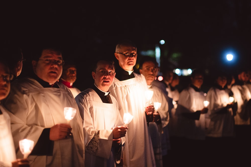 priests holding lighted candles at night