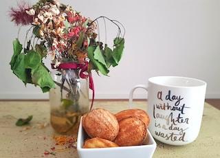 baked bread on white ceramic bowl beside mug and flower centerpiece