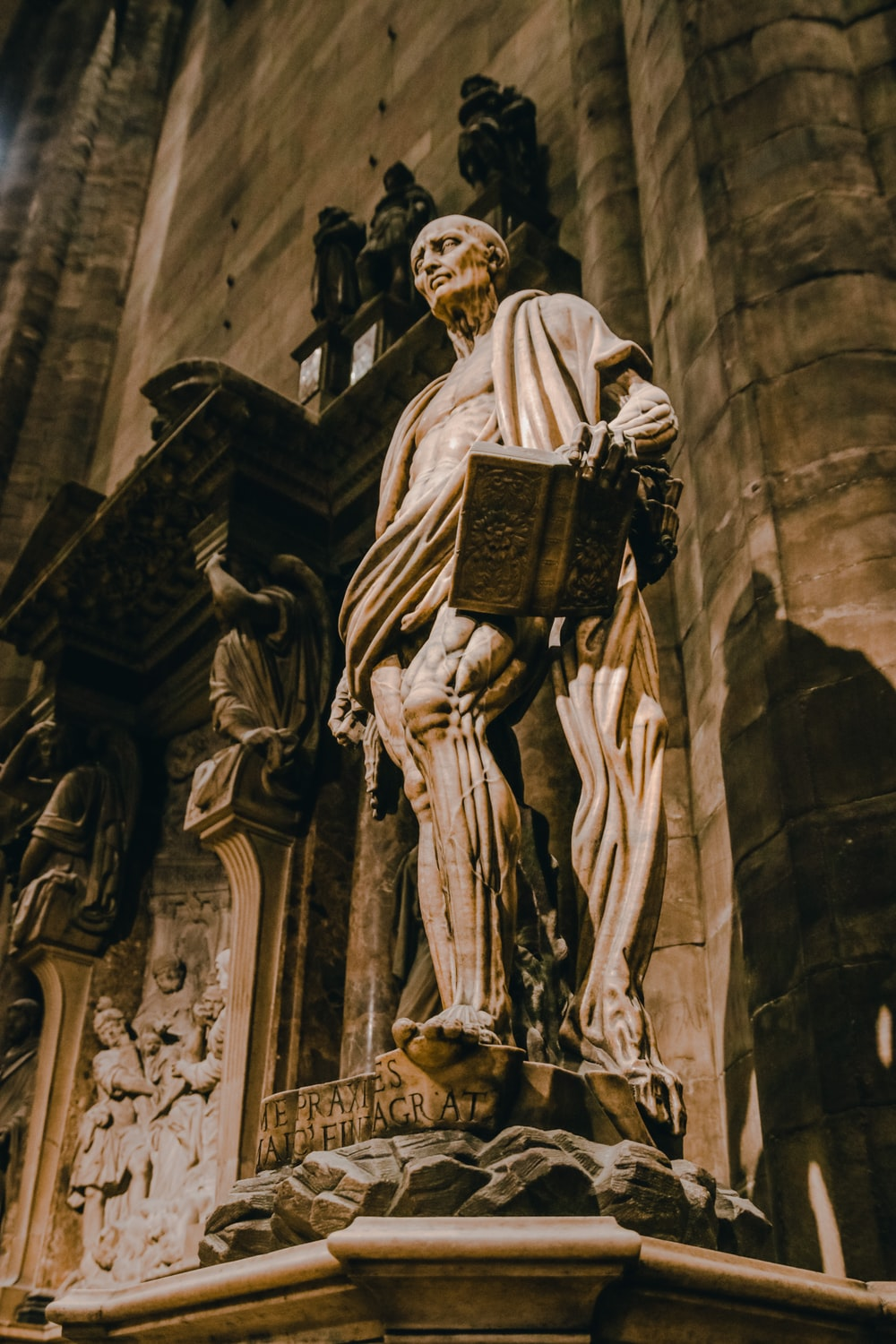 low-angle photography of man carrying a book statue