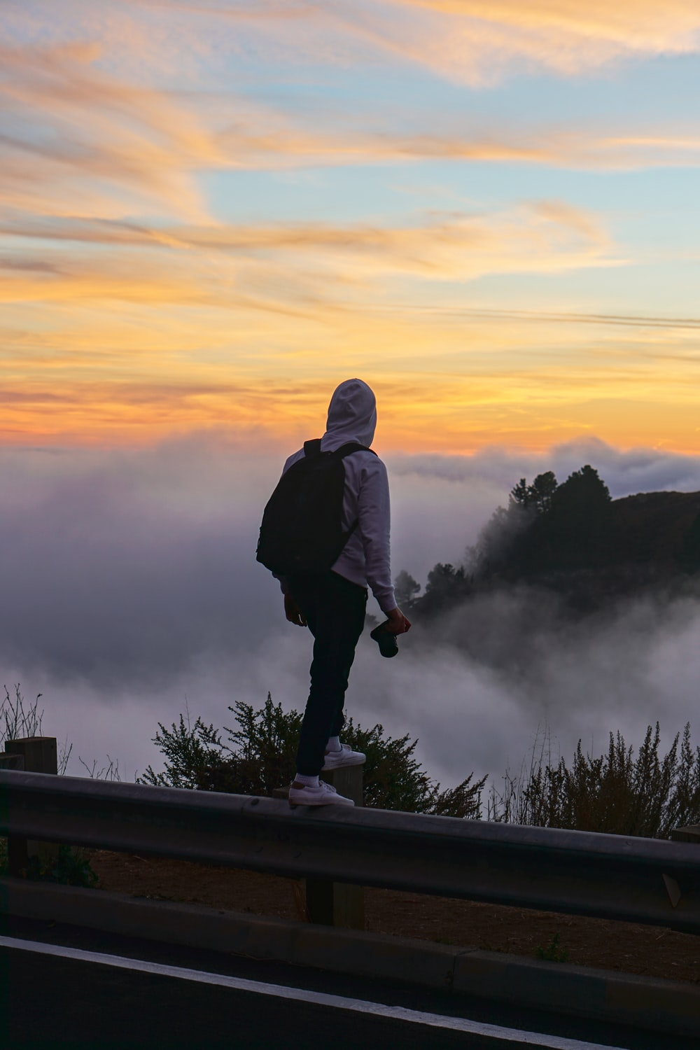 man standing on a fence overlooking sea of clouds