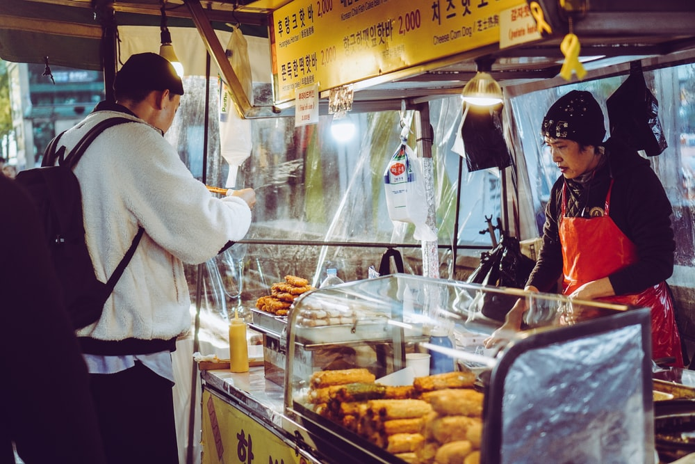 man eating food in front of food ventor at night
