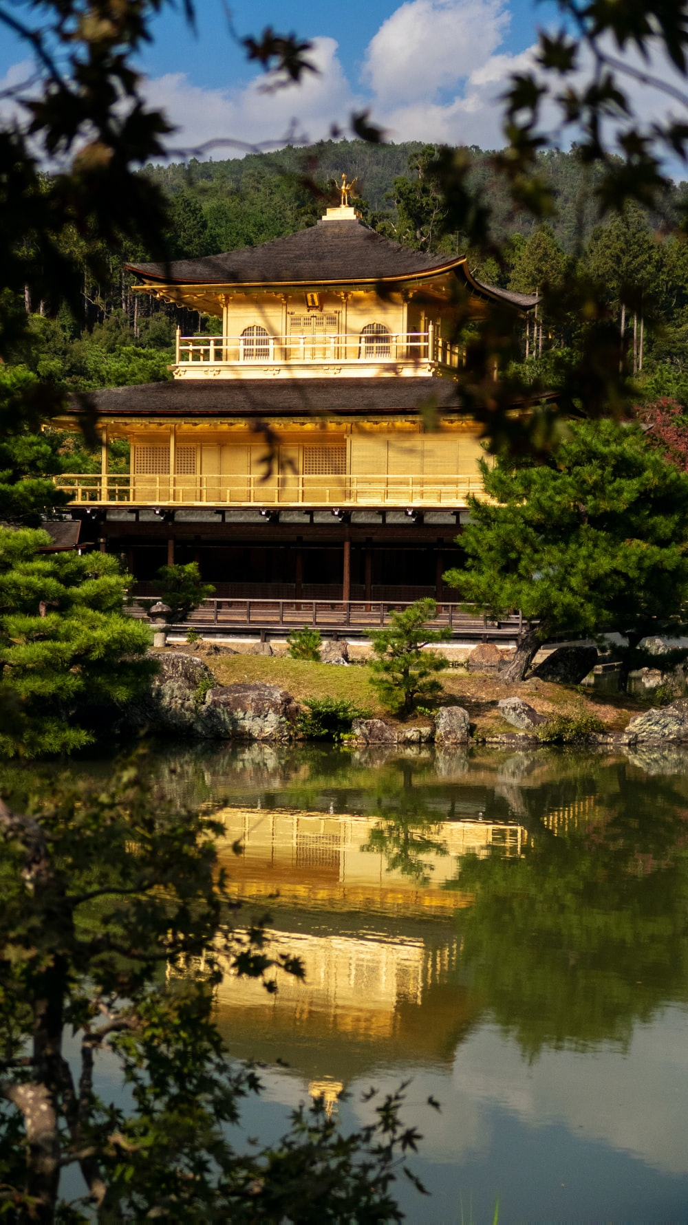 yellow and black temple between trees facing body of water