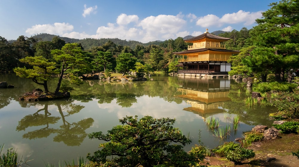 temple above water near trees during day