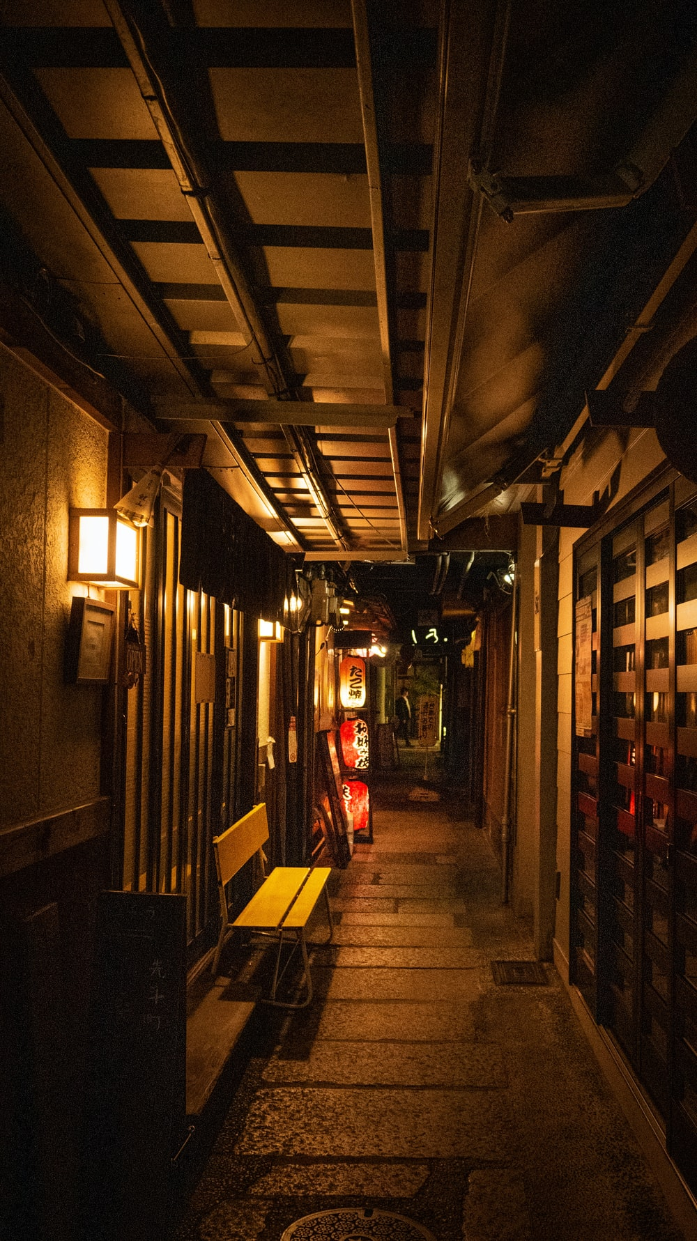 narrow pathway lighted with sconces