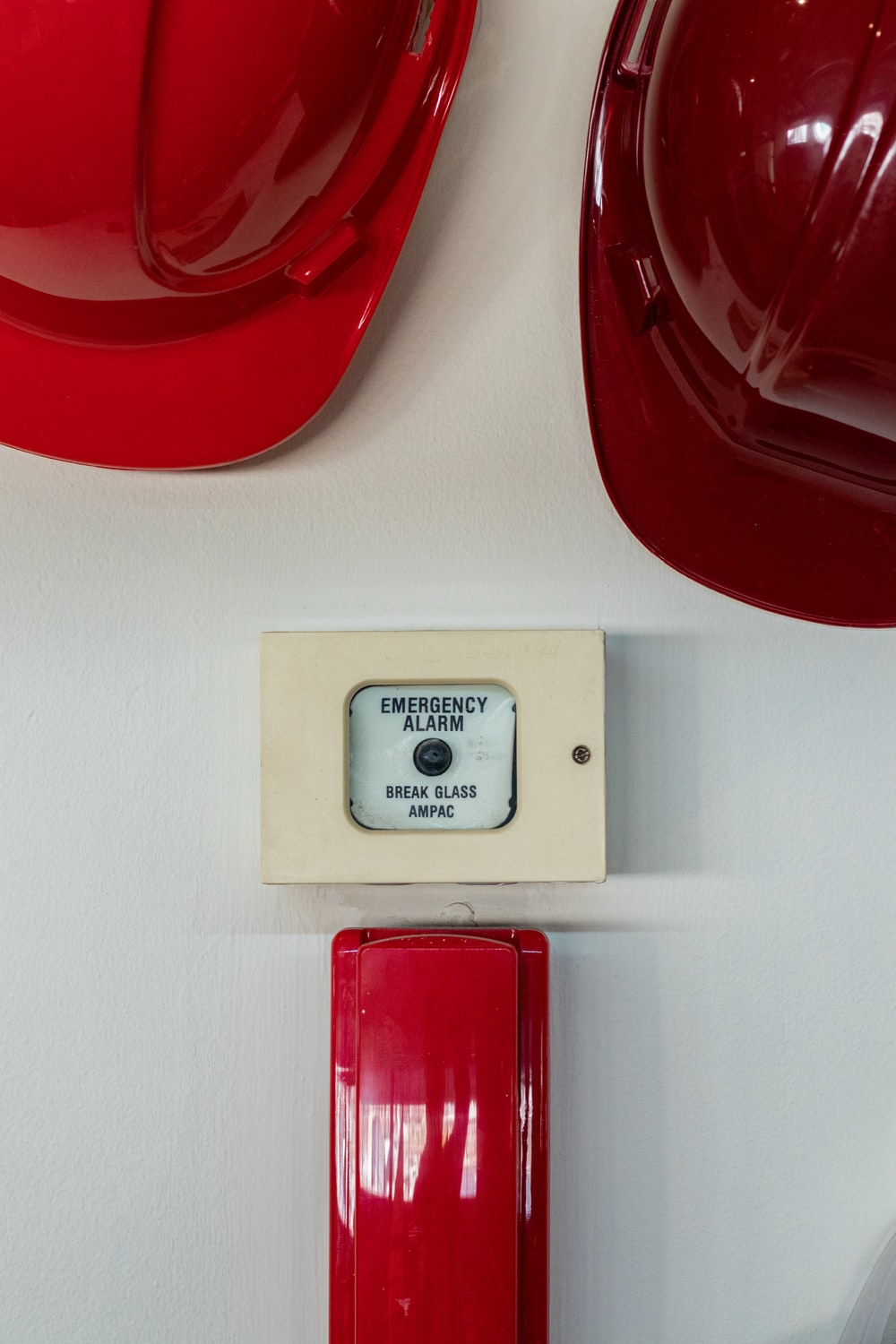 two red hard hats near emergency alarm button