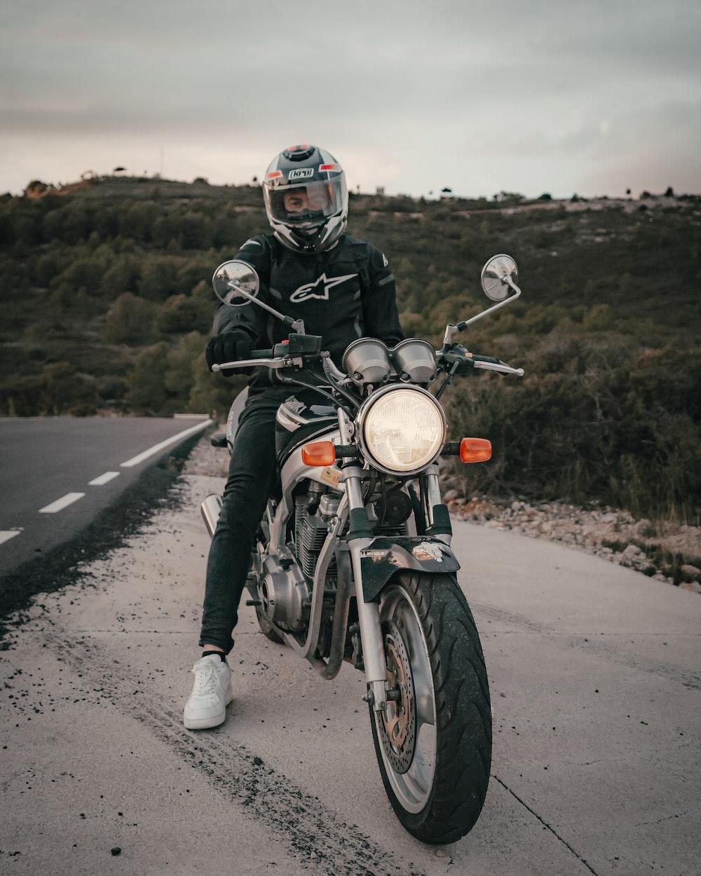man wearing black and white Alpinestar jacket riding motorcycle near road