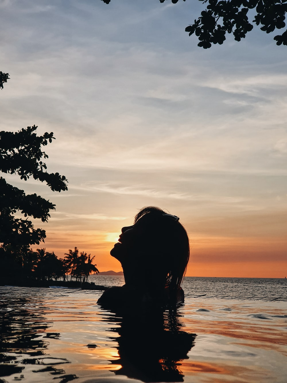 silhouette of woman in body of water during golden hour