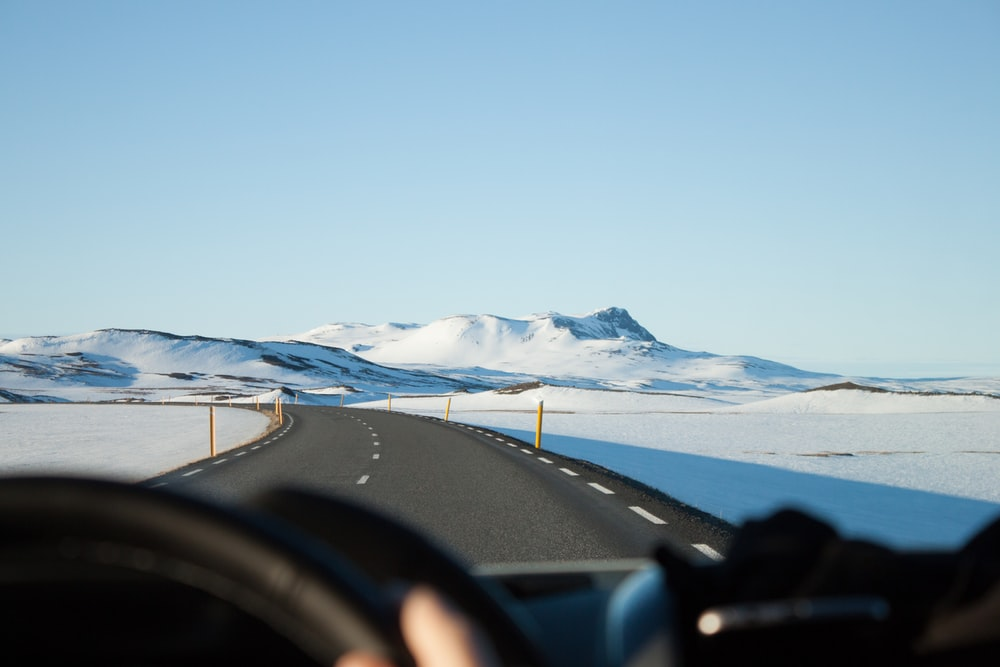 person riding vehicle on paved road between snow field