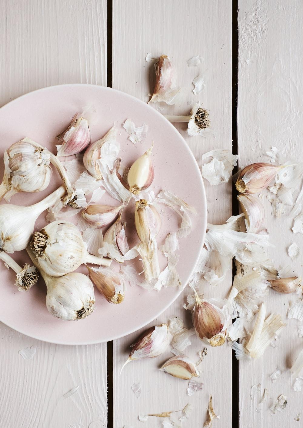 garlic cloves on round white plate