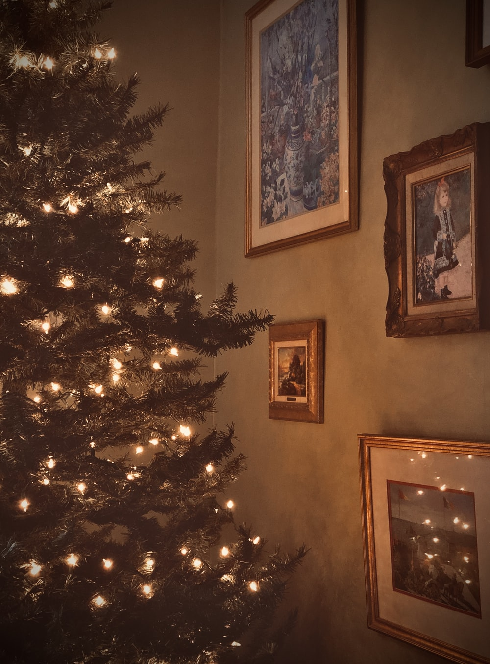 Christmas tree with turned on mini string lights near wall of pictures
