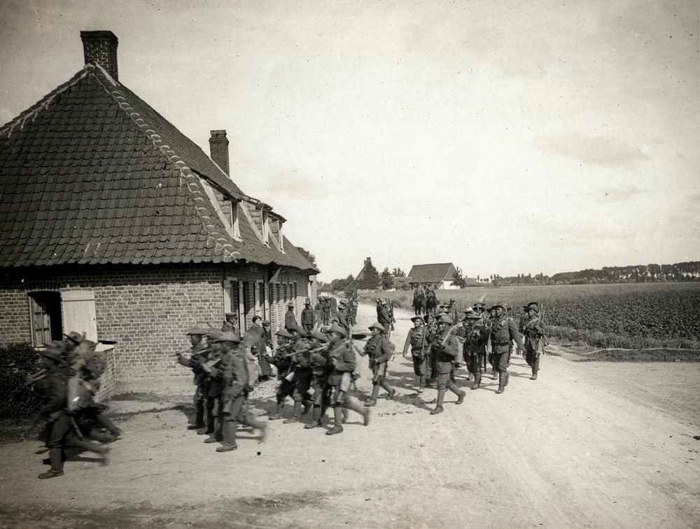 grayscale photo of men standing beside houses