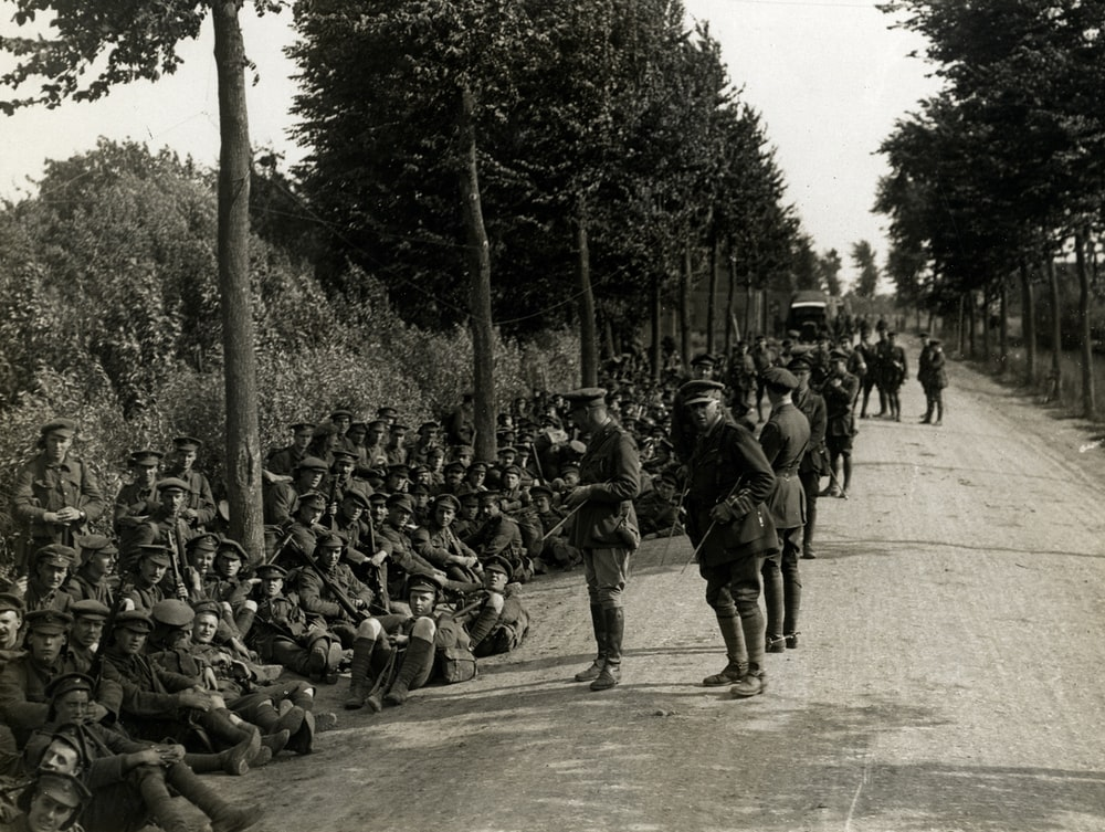 grayscale photography of soldiers sitting near road and others are standing