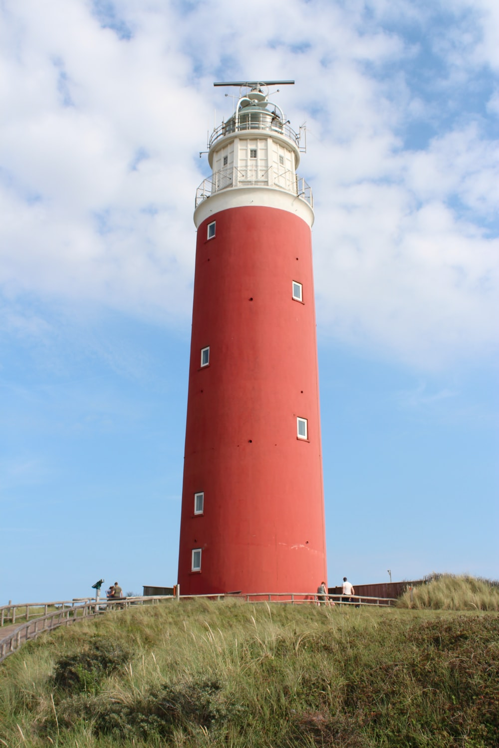 low-angle photography of a red and white lighthouse