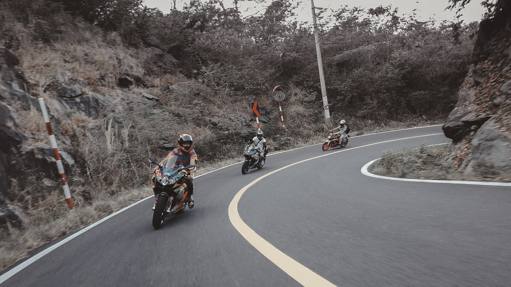 motorcyclist on road by rocks