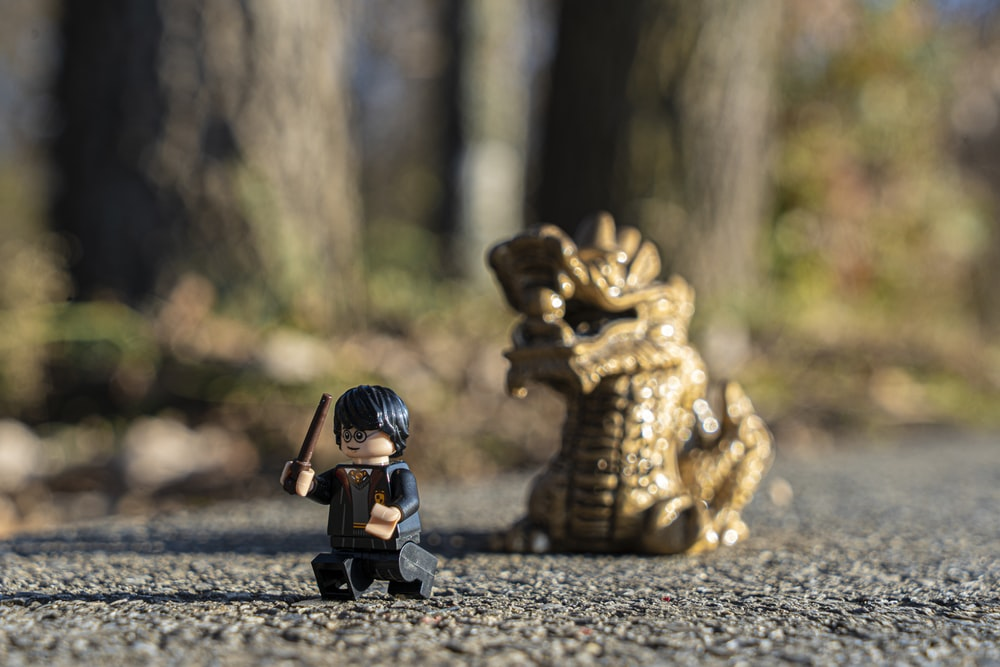 selective focus photography of Harry Potter minifig by dragon figure on pavement