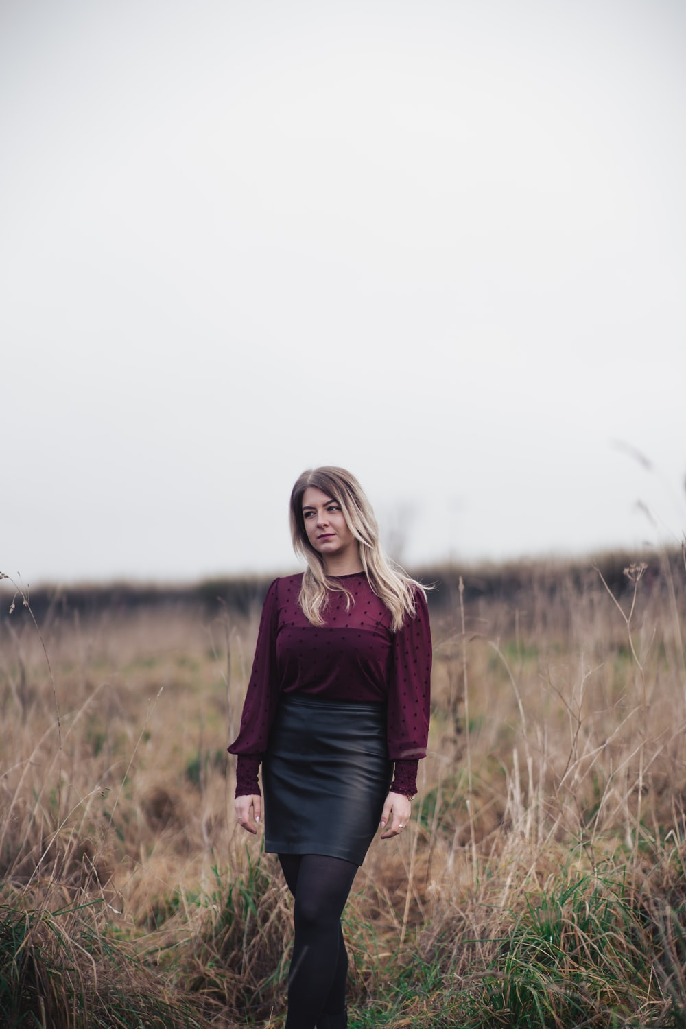 woman in red long-sleeved top and black skirt standing outdoors