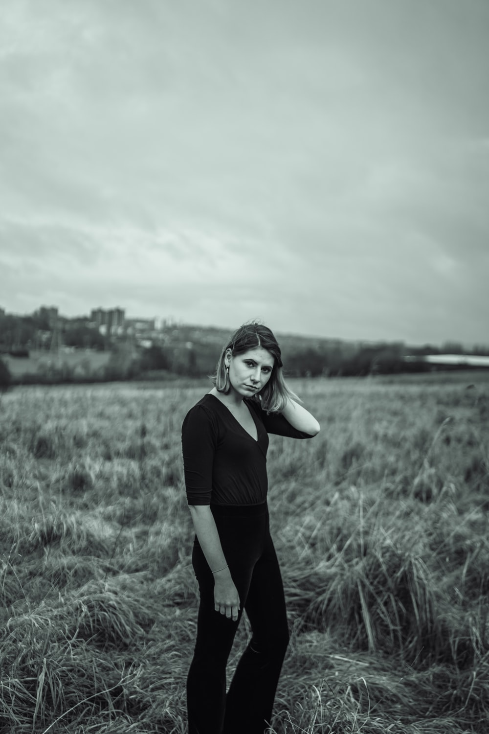 grayscale photography of woman in a grass field