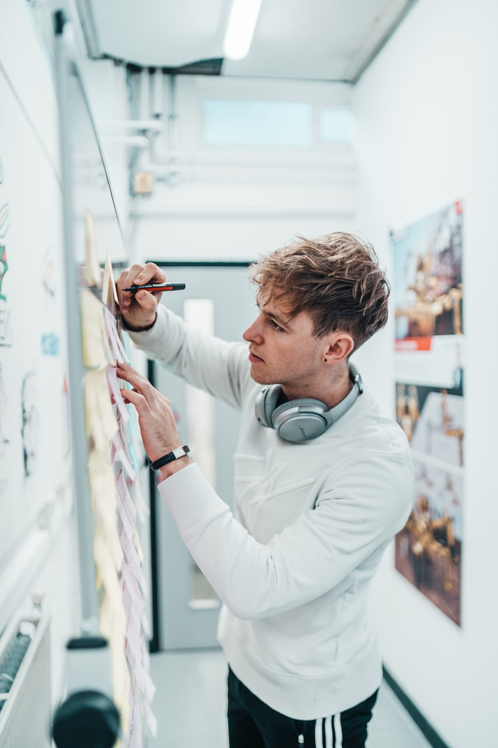 man with pen writing on wall