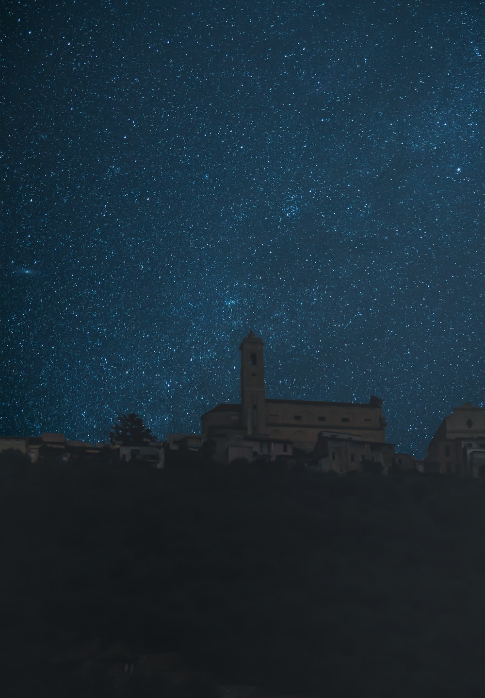 low-angle photography of church under a starry night sky